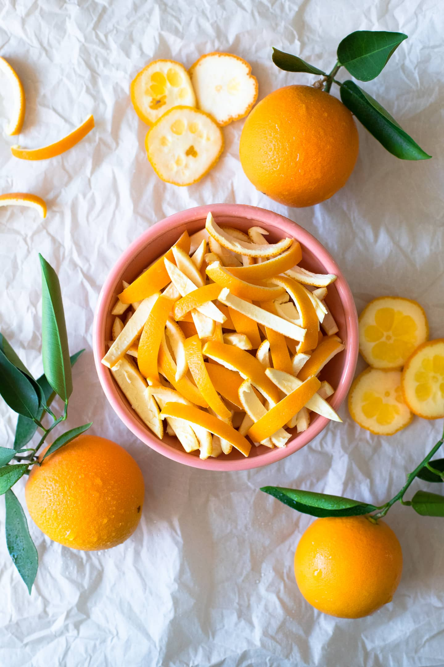 Overhead view of strips of orange peel in a bowl, surrounded by more oranges and peel cuttings.