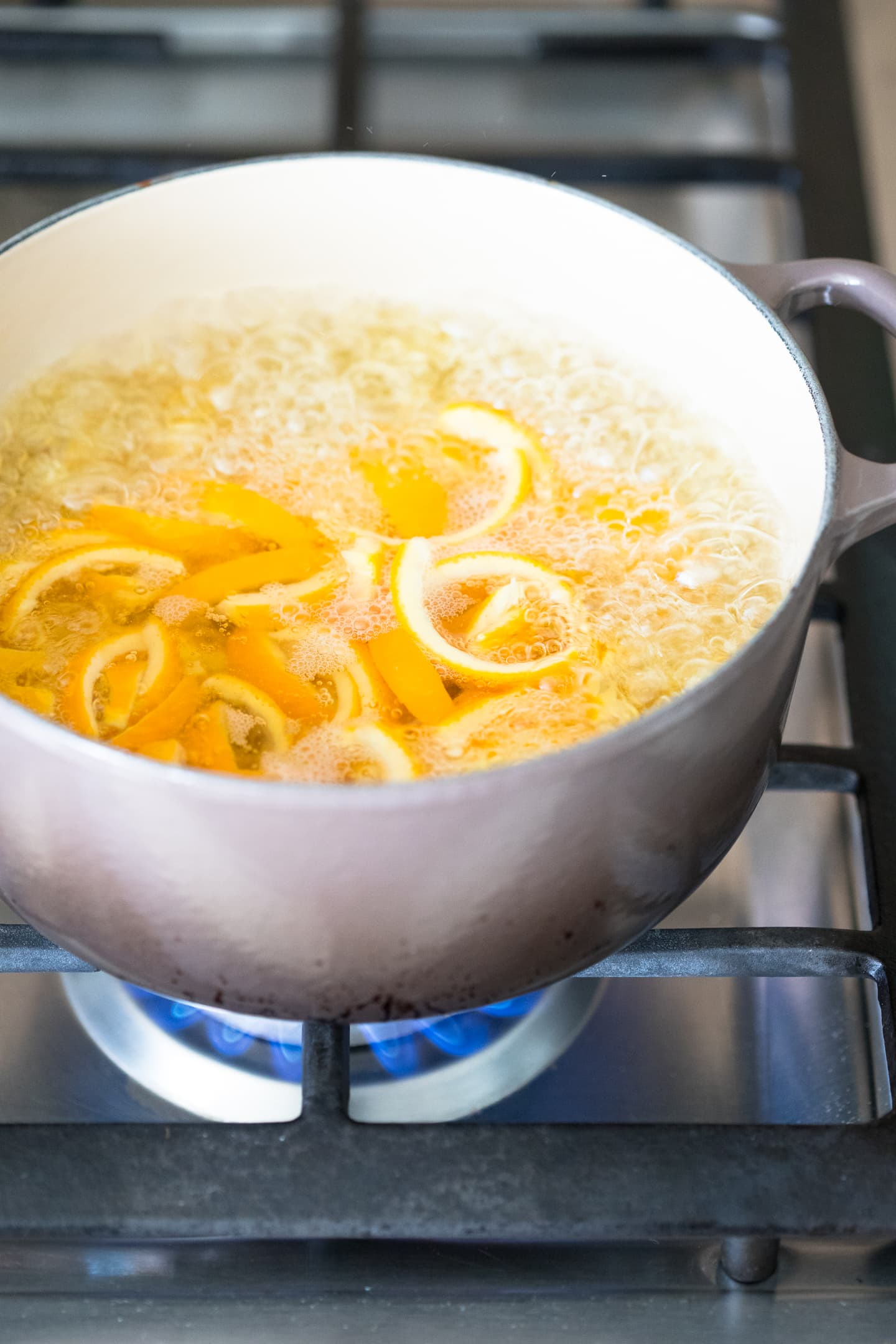 Angled view of orange peels being balanced in a pot on the stove.