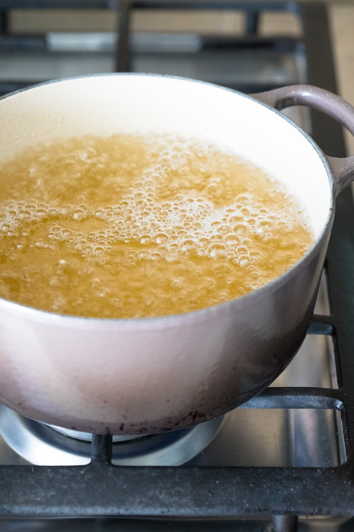 Angled view of sugar syrup simmering in a pot on the stove.