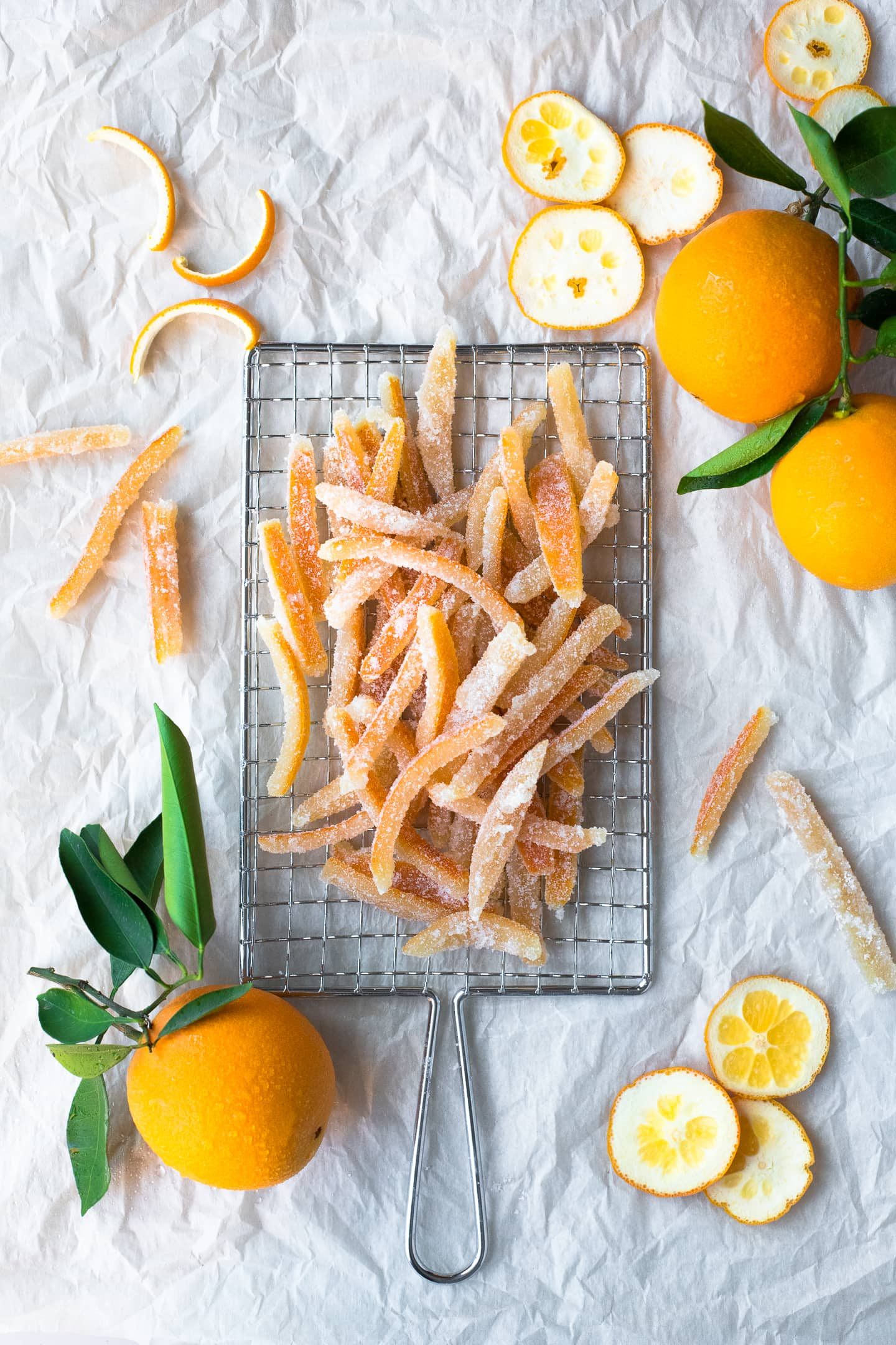 Overhead view of strips of candied orange peel on a safety grater, surrounded by more oranges and peel cuttings.