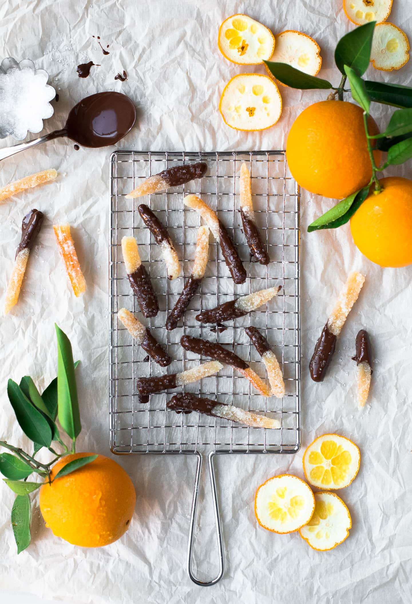 Overhead view of strips of chocolate-dipped candied orange peel on a safety grater, surrounded by more oranges and peel cuttings.