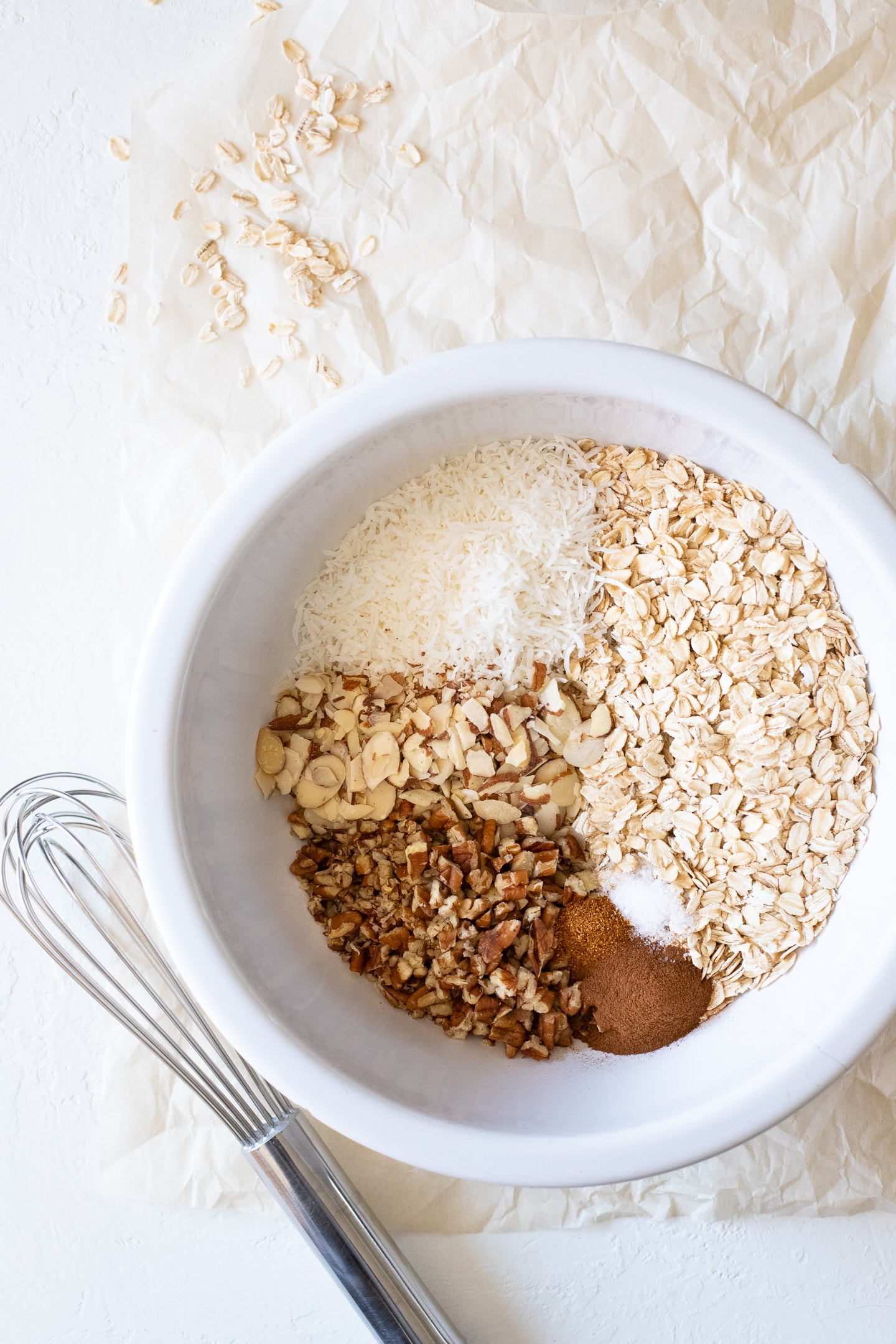 Overhead view of the ingredients for making Easy Homemade Granola in a large white bowl, with a whisk and scattered oats on the side.