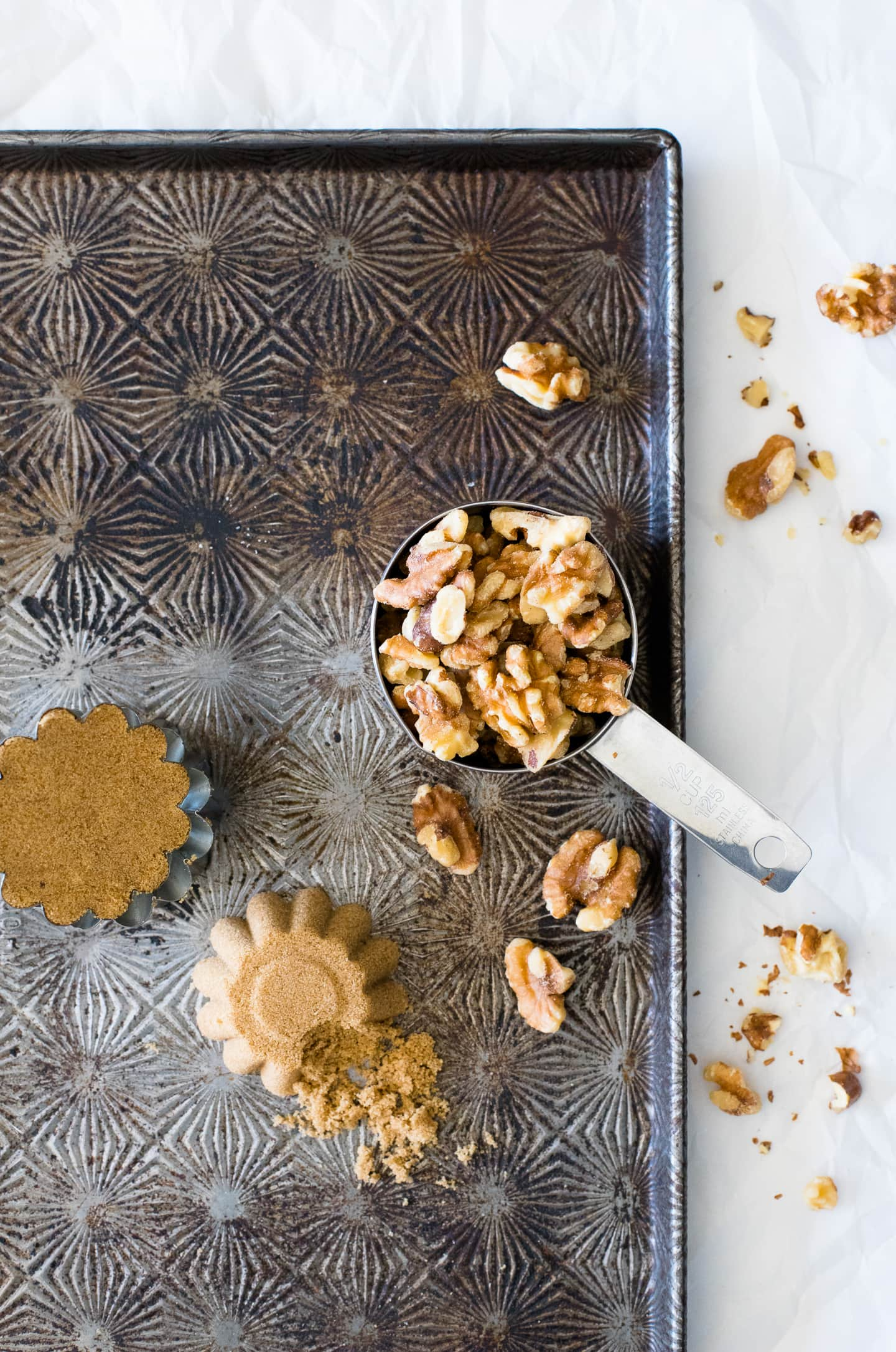 Overhead view of walnuts in a measuring cup, sitting on a vintage tray along with other recipe ingredients: brown sugar and sea salt.