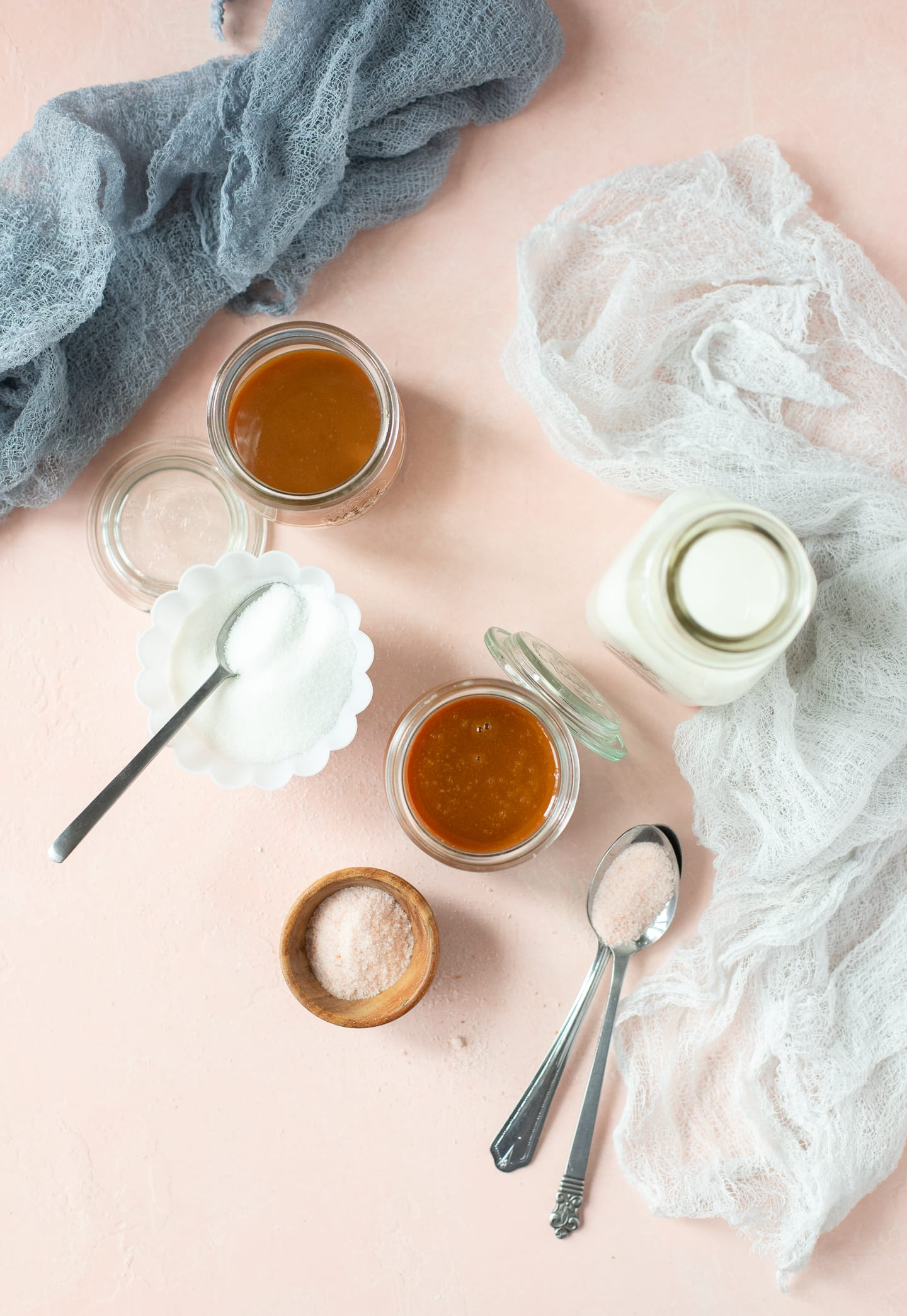 Overhead view of two jars of caramel sauce with milk, sugar, and sea salt surrounding them.
