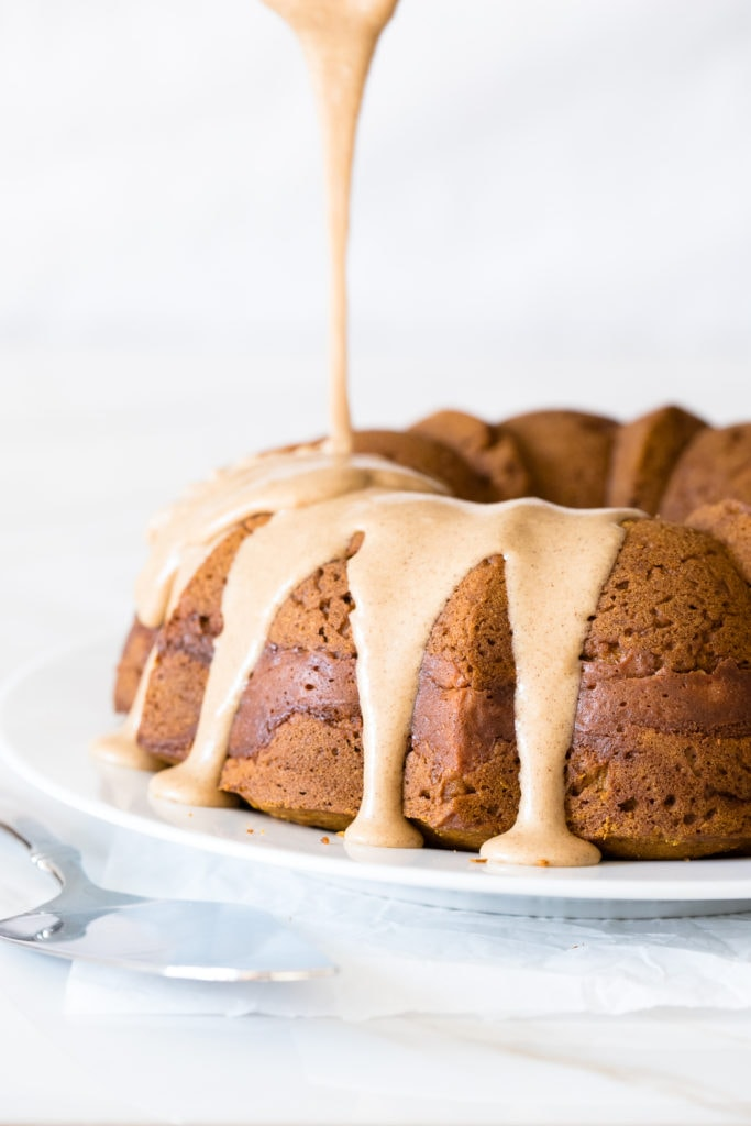 Front-facing view of brown sugar icing being poured over a pumpkin bundt cake.