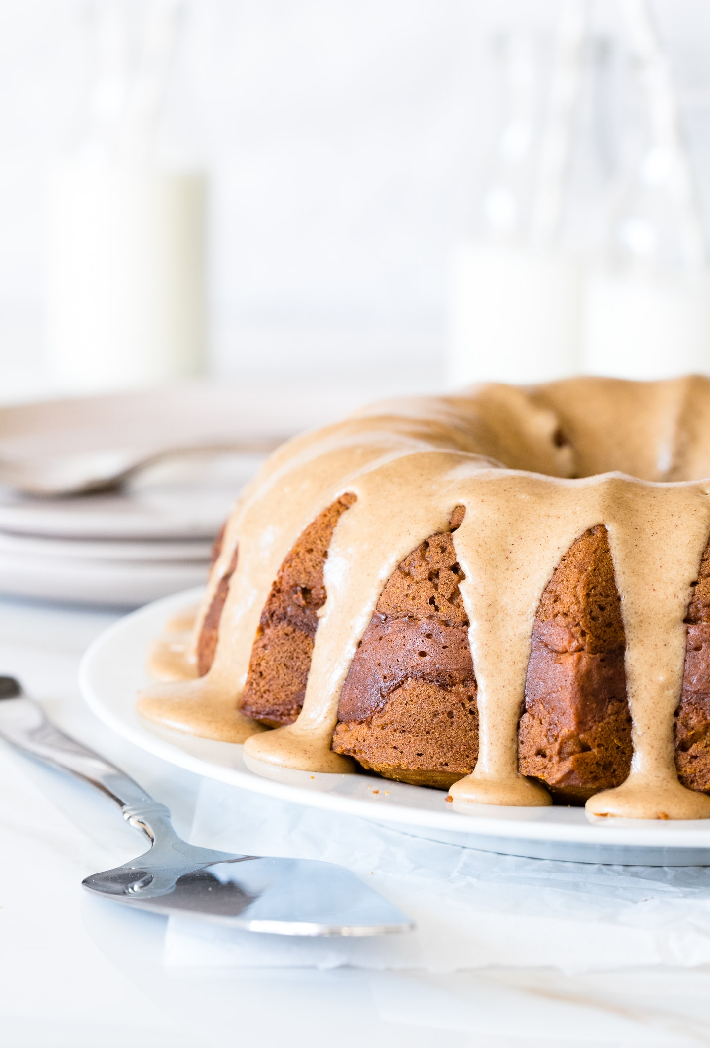 Front-facing view of a pumpkin bundt cake topped with a brown sugar glaze, ready to serve on a white plate with a serving spatula placed nearby.