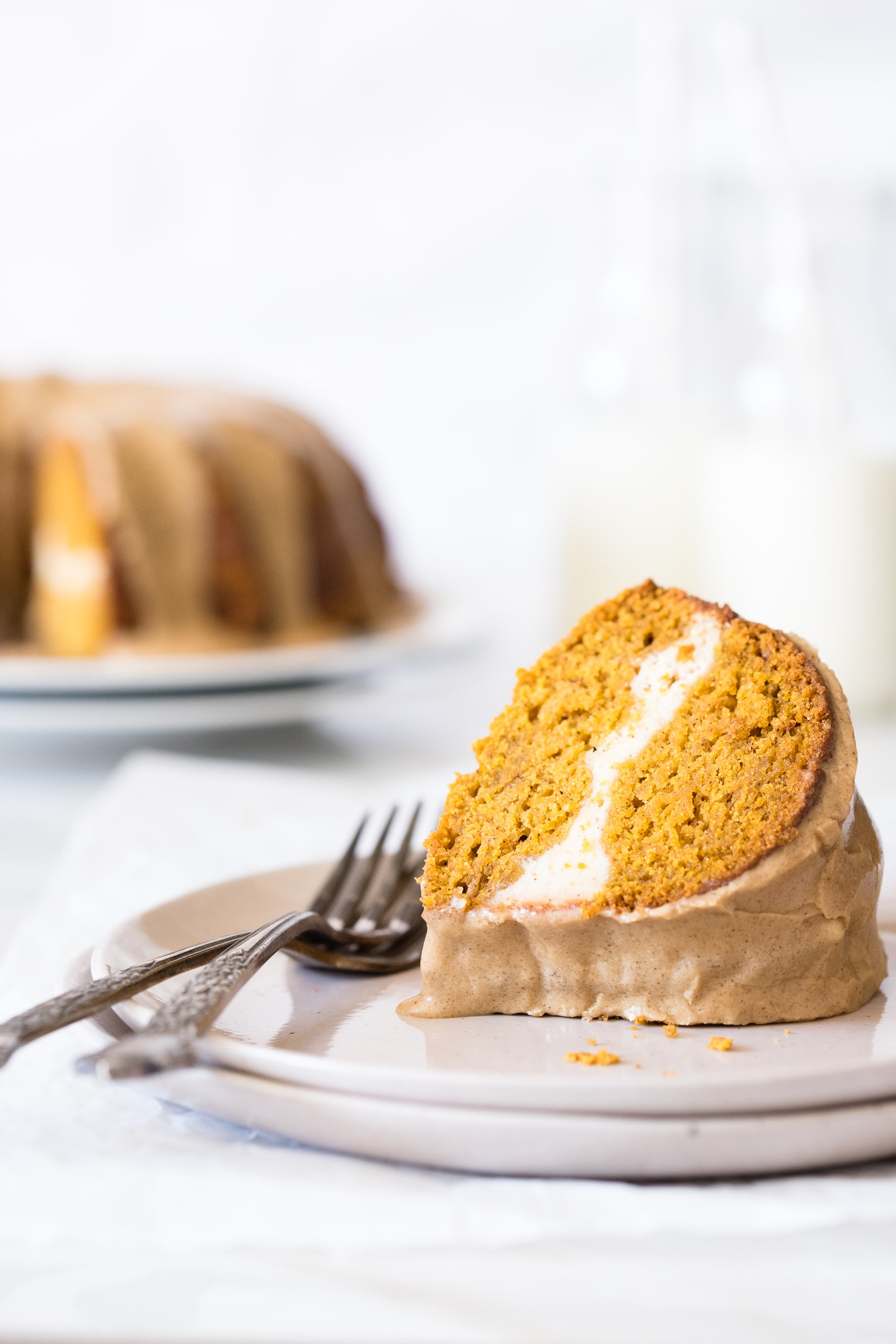 Slice of pumpkin bundt cake on two-stacked plates, with the full cake and a glass of milk in the background.