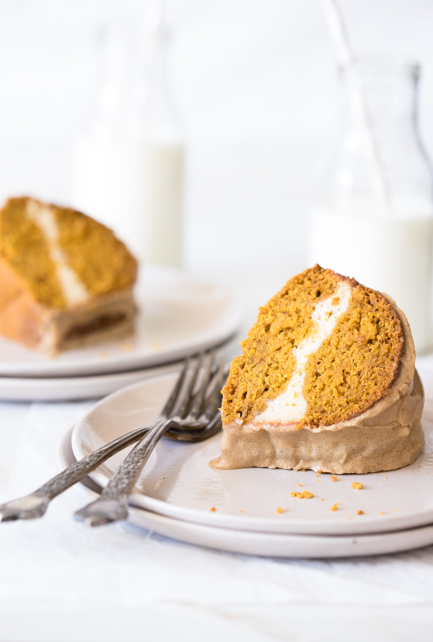 Two slices of pumpkin bundt cake on cream-colored plates, one in the foreground and one in the background.