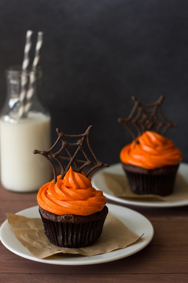 Front-facing view of two Pumpkin Halloween Cupcakes featuring pumpkin-chocolate cupcakes with orange-colored cream cheese frosting topped with chocolate spiderwebs, plus a bottle of milk in the background.