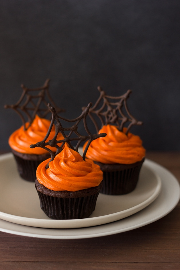 Front-facing view of three pumpkin Halloween cupcakes featuring pumpkin chocolate cupcakes with orange-colored cream cheese frosting and topped with chocolate spiderwebs, sitting on top of two stacked plates.