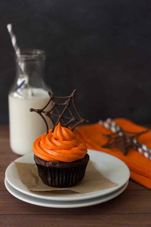 Front-facing view of one Pumpkin Halloween Cupcake featuring pumpkin-chocolate cake with orange-colored cream cheese frosting topped with a chocolate spiderweb, sitting on top of two stacked white plates. A bottle of milk and grey paper straws are in the background.