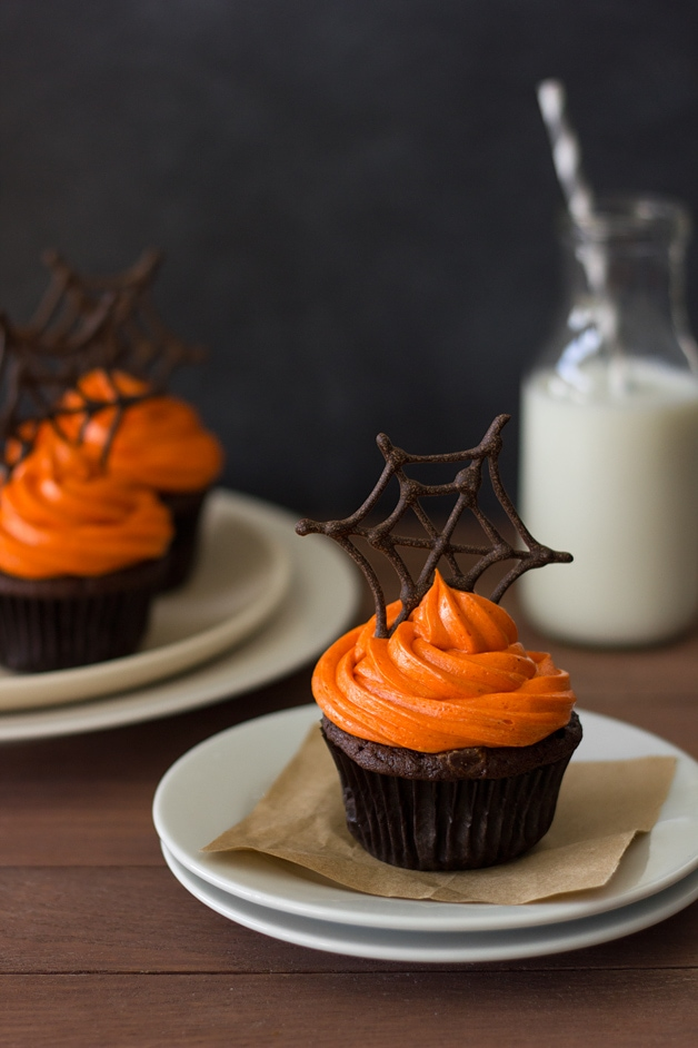 Front-facing view of a Pumpkin Halloween Cupcake featuring pumpkin-chocolate cake with orange-colored cream cheese frosting topped with a chocolate spiderwebs. Two more cupcakes and a bottle of milk are in the background.