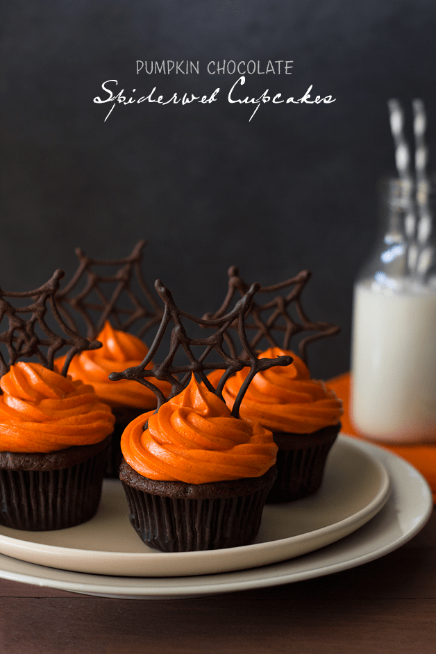 Front-facing view of pumpkin Halloween cupcakes featuring pumpkin chocolate cupcakes with orange-colored cream cheese frosting and topped with chocolate spiderwebs, plus a glass of milk in the background.