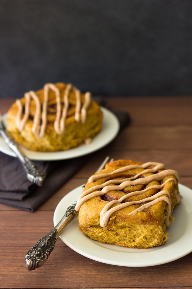 Pumpkin Spice Cinnamon Rolls with Cinnamon Cream Cheese Drizzle - pillowy-soft cinnamon rolls filled with warm fall spices, perfect for a chilly weekend morning! from @brighteyedbaker | Confessions of a Bright-Eyed Baker