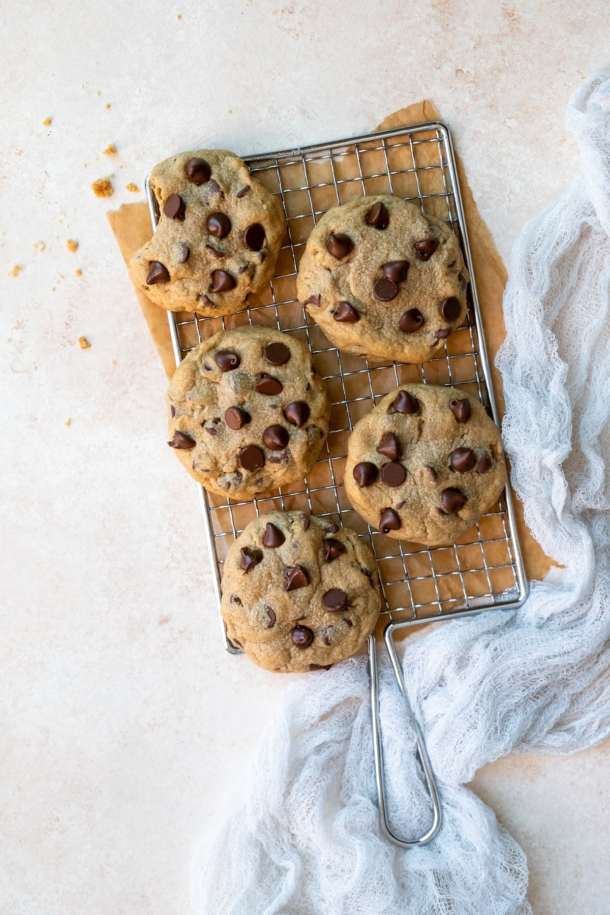 Cookies on a metal grater, set over a brown piece of parchment, with a white linen to the side.