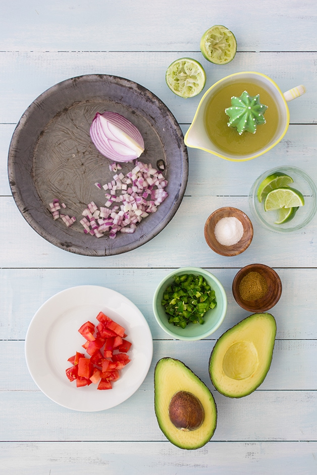 A recipe for fresh, spicy guacamole loaded with red onion, tomato, and a touch of lime juice for maximum flavor. Takes minutes to make and SO much better than store-bought! | www.brighteyedbaker.com