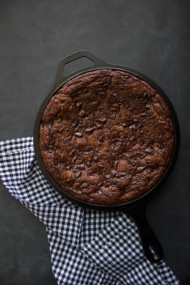 Overhead view of a skillet brownie next to a checkered linen over a black backdrop.