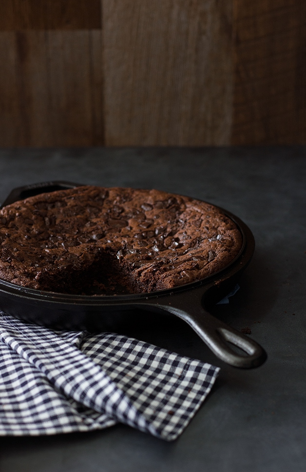 Angled view of a skillet brownie next to a checkered linen over a black backdrop.
