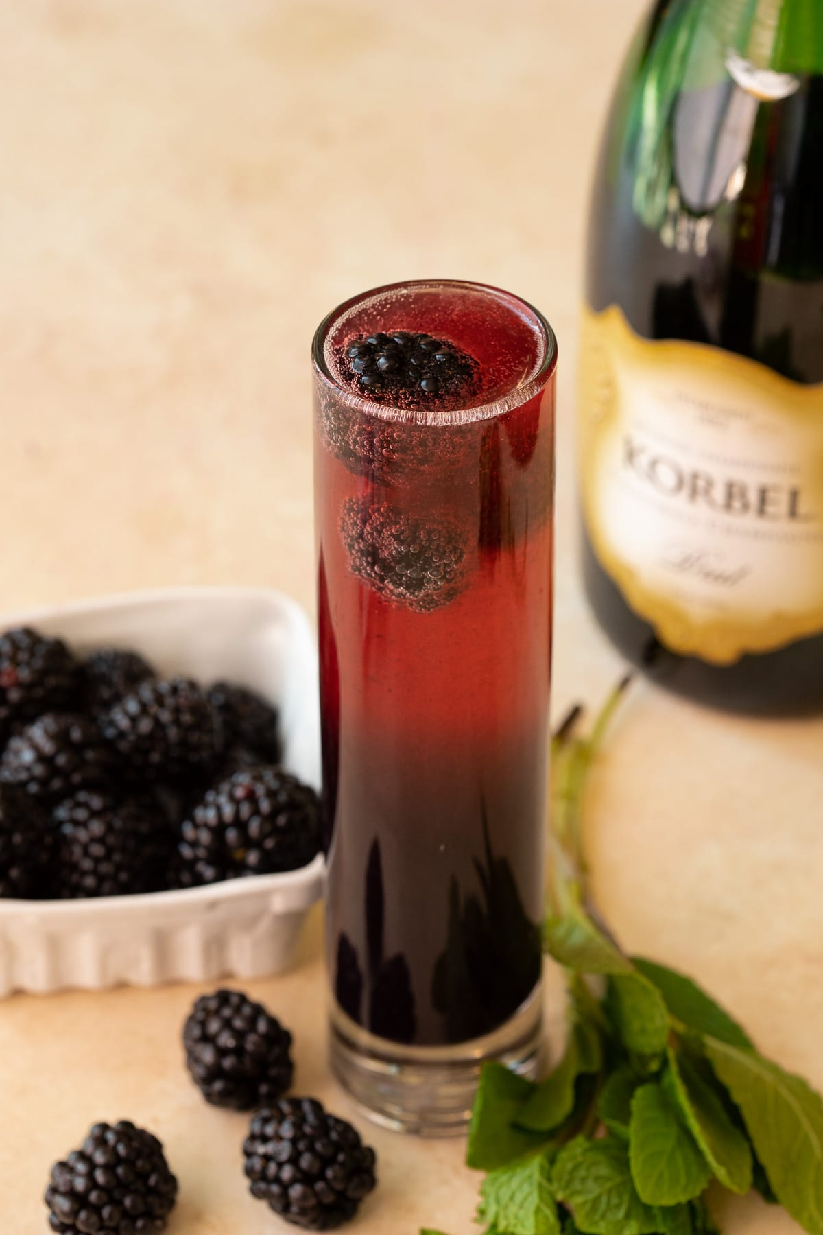 Mimosa with fresh blackberries and mint garnish.
