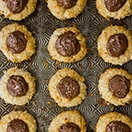 Nutella-Filled Coconut Thumbprint Cookies - Like a shortbread cookie-turned-macaroon, with sweet, toasted coconut on the outside and a dollop of Nutella in the middle for a nutty chocolate twist.   www. brighteyedbaker.com