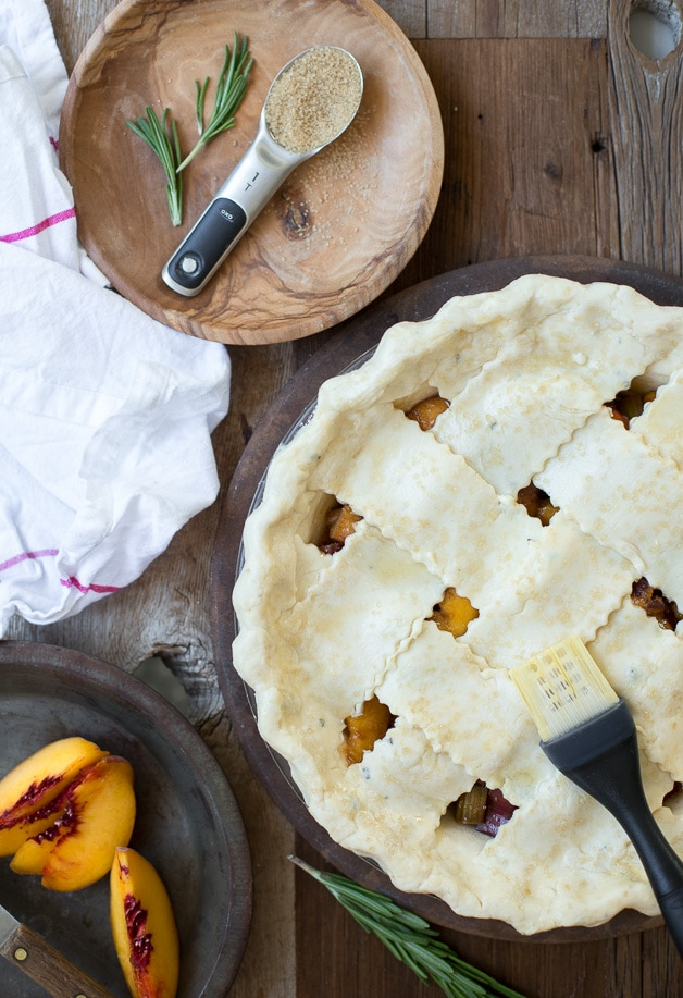 A classic pie with a buttery gluten-free crust and tangy-sweet rhubarb-peach filling, topped with a fluffy cloud of rosemary whipped cream. Refined sugar-free!