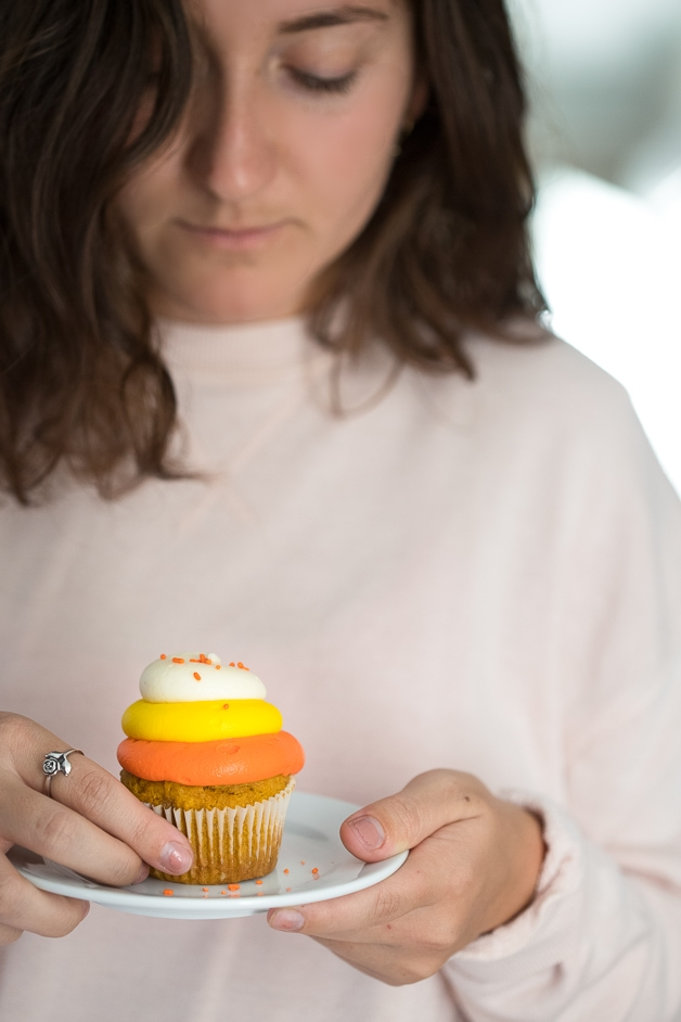 Front-facing view of a girl holding a gluten-free pumpkin cupcake with frosting decorated in candy corn colors.