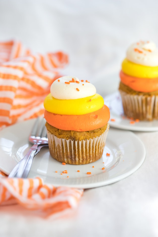 Front angled view of two gluten-free pumpkin cupcake with cream cheese frosting colored to resemble candy corn.