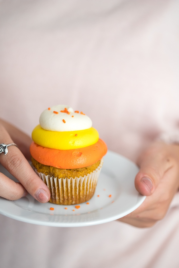 Close up of a gluten-free pumpkin cupcake with candy corn-colored frosting on a plate in girl's hands.