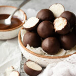 Easy-to-make coconut bites dipped in dark chocolate -- a perfect guilt-free sweet treat! {keto, gluten-free, vegan}