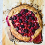 A galette topped with mixed berries on a sheet of parchment.