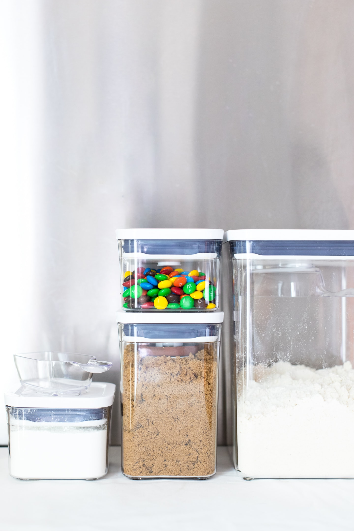 Front-facing view of OXO POP containers holding flour, brown sugar, cornstarch, and M&M's.