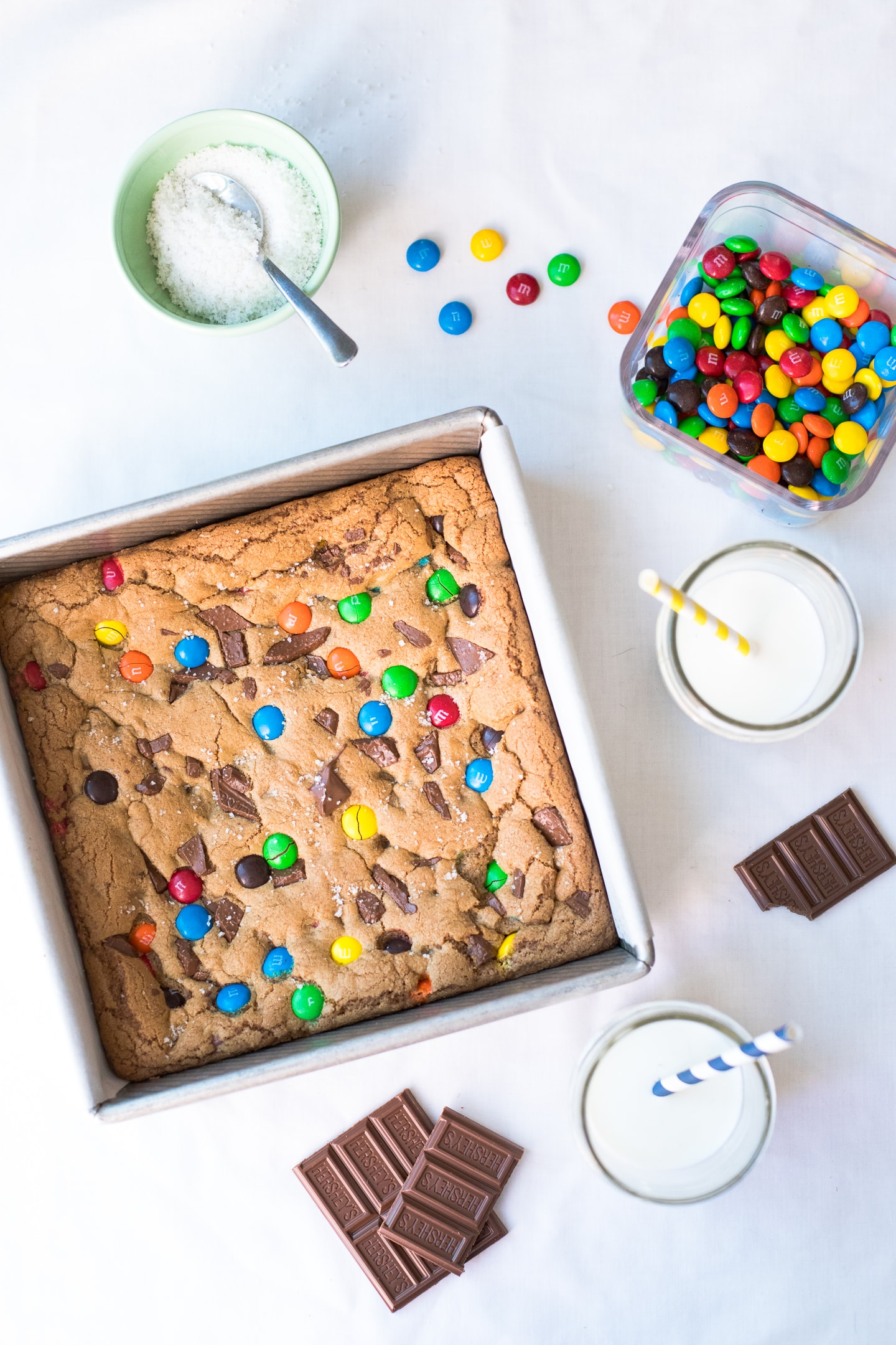 Overhead view of Salted Candy Bar Blondies in a baking pan, with glasses of milk, candy, and a bowl of fleur de sel on the side.