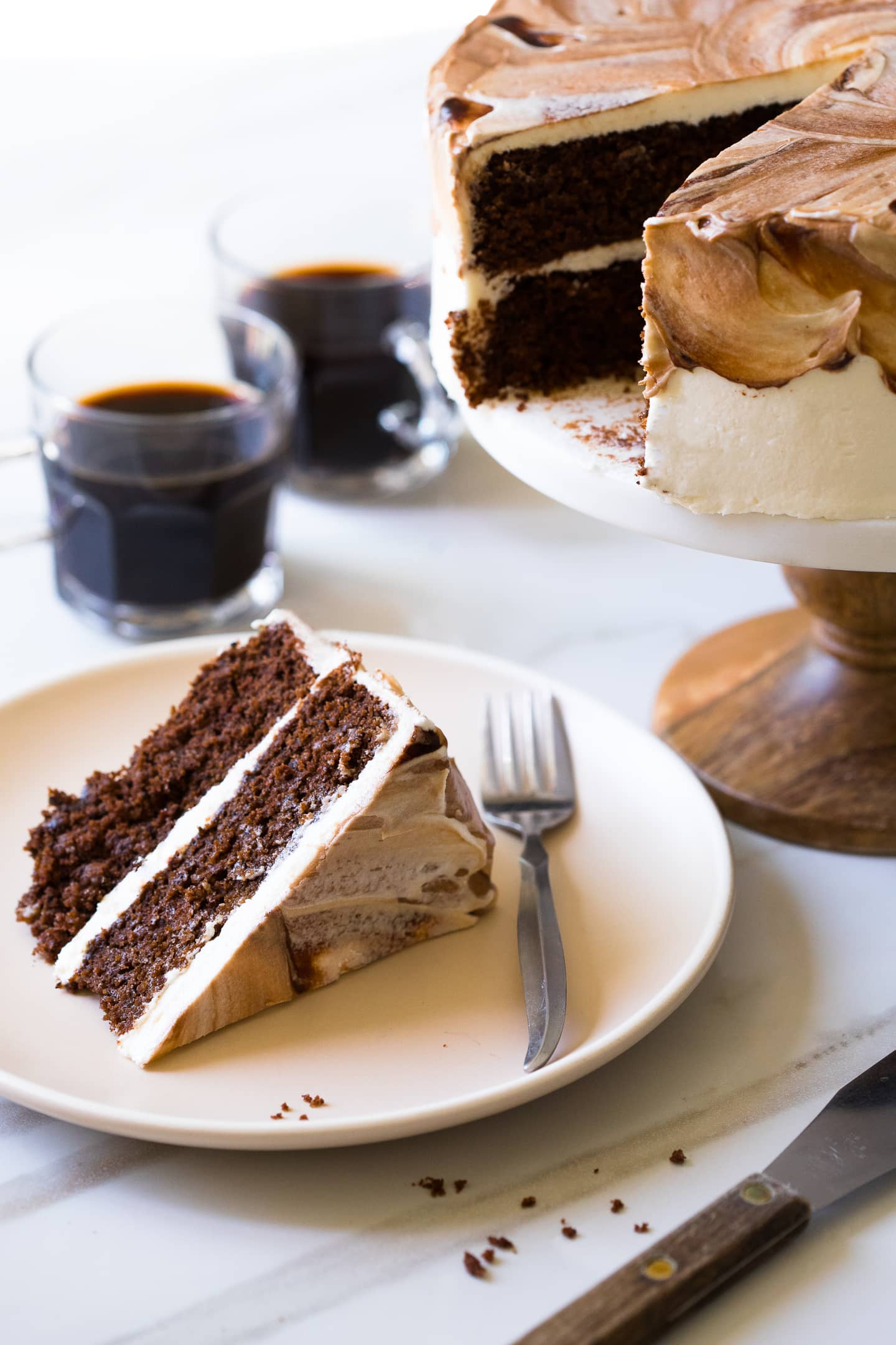 Front-angled view of a slice of Vietnamese Coffee Cake on a cream-colored plate, plus two cups of coffee and the full cake in the background.