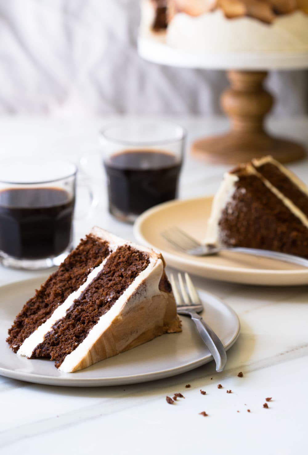 Front-facing view of two slices of Vietnamese Coffee Cake on cream-colored plates, plus two cups of coffee in the background.