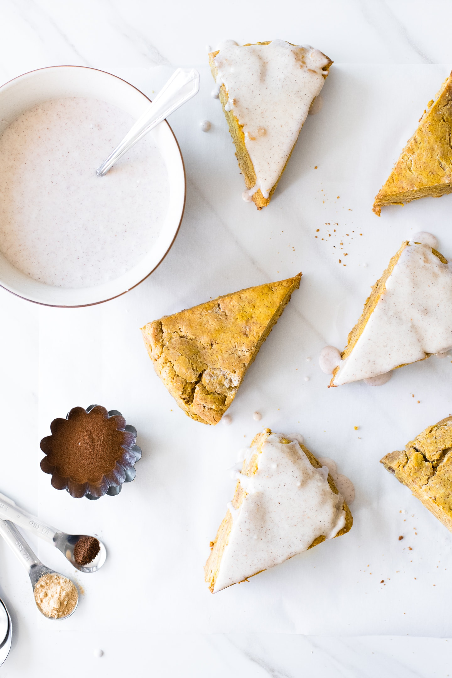 Overhead view of pumpkin scones on a white background. Some scones are glazed with a pumpkin spice glaze, and a bowl of glaze sits off to the side.