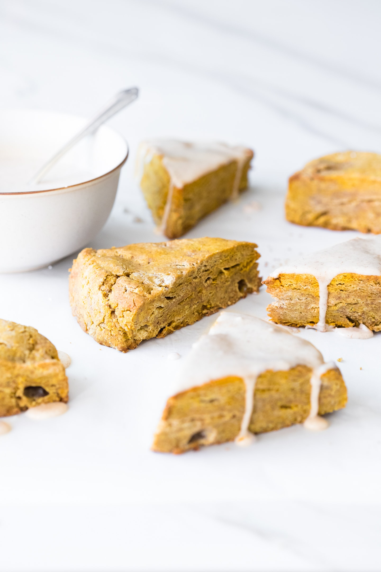 Front-angled view of pumpkin scones on a white backdrop, some top with a pumpkin spice glaze. A bowl of glaze is in the corner.