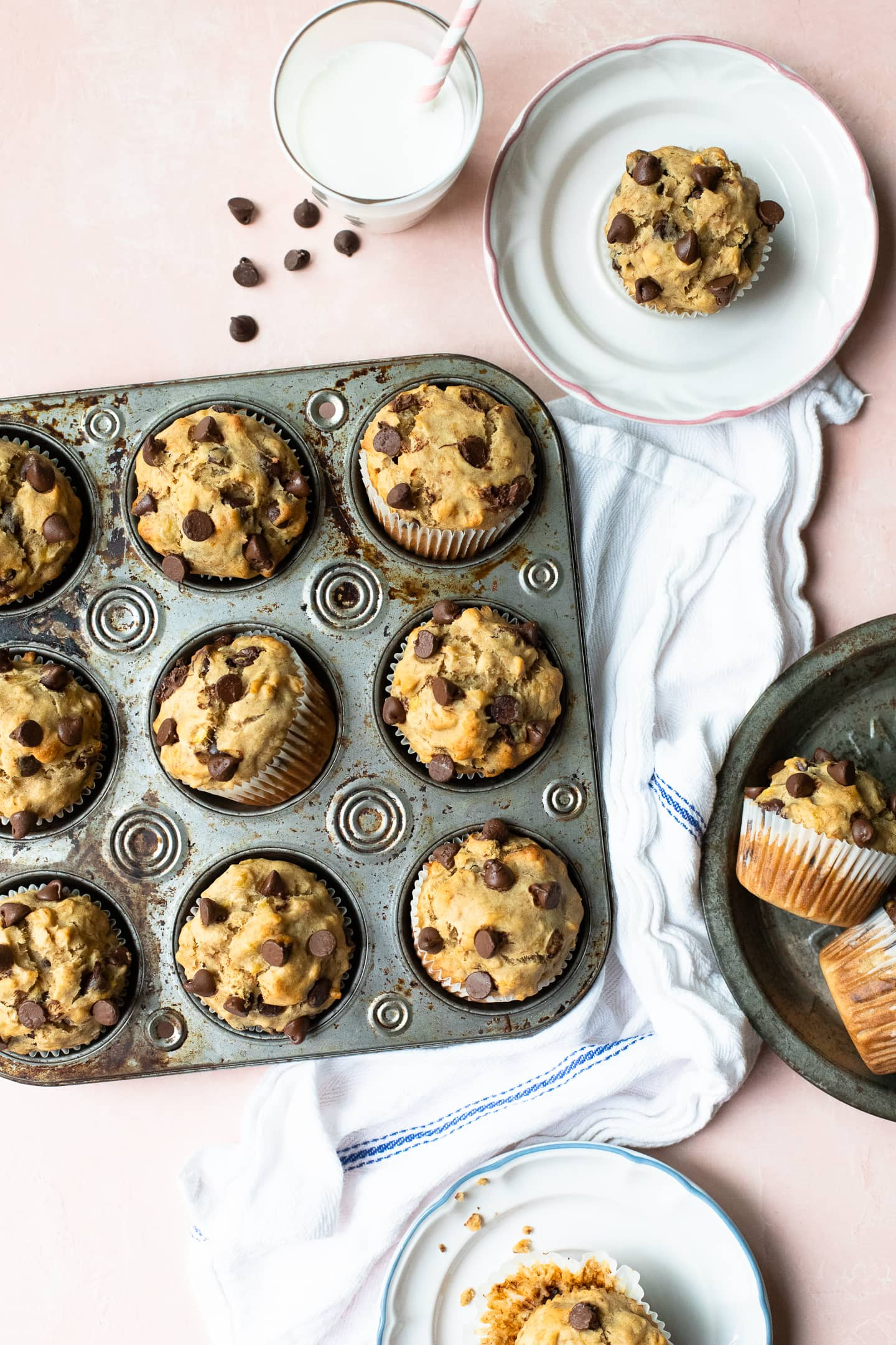 Overhead view of Peanut Butter Banana Chocolate Chip Muffins in a muffin tray, along with extra muffins on plates, over a light pink backdrop.