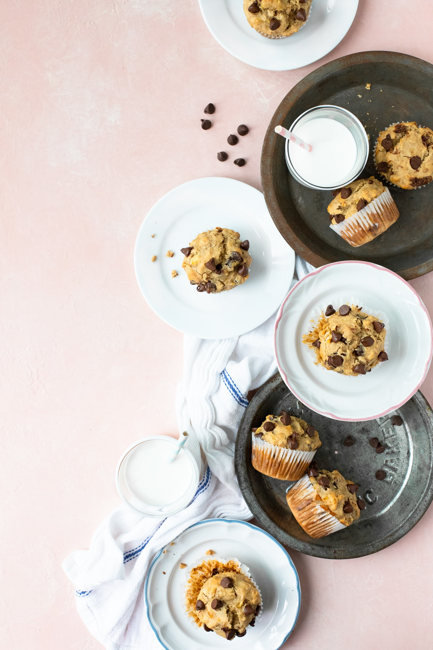 Flatlay view of Peanut Butter Banana Chocolate Chip Muffins on various plates, along with a white linen, glasses of milk, and scattered chocolate chips, on a light pink backdrop.