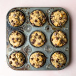 Overhead view of Peanut Butter Banana Chocolate Chip Muffins in a muffin pan on a light pink backdrop.