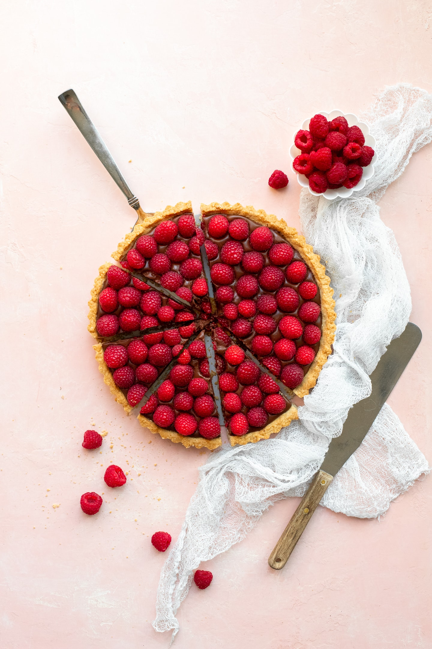 Overhead view of a Raspberry Chocolate Tart, sliced and ready to serve, surrounded by extra raspberries, a white linen, and a pallet knife.