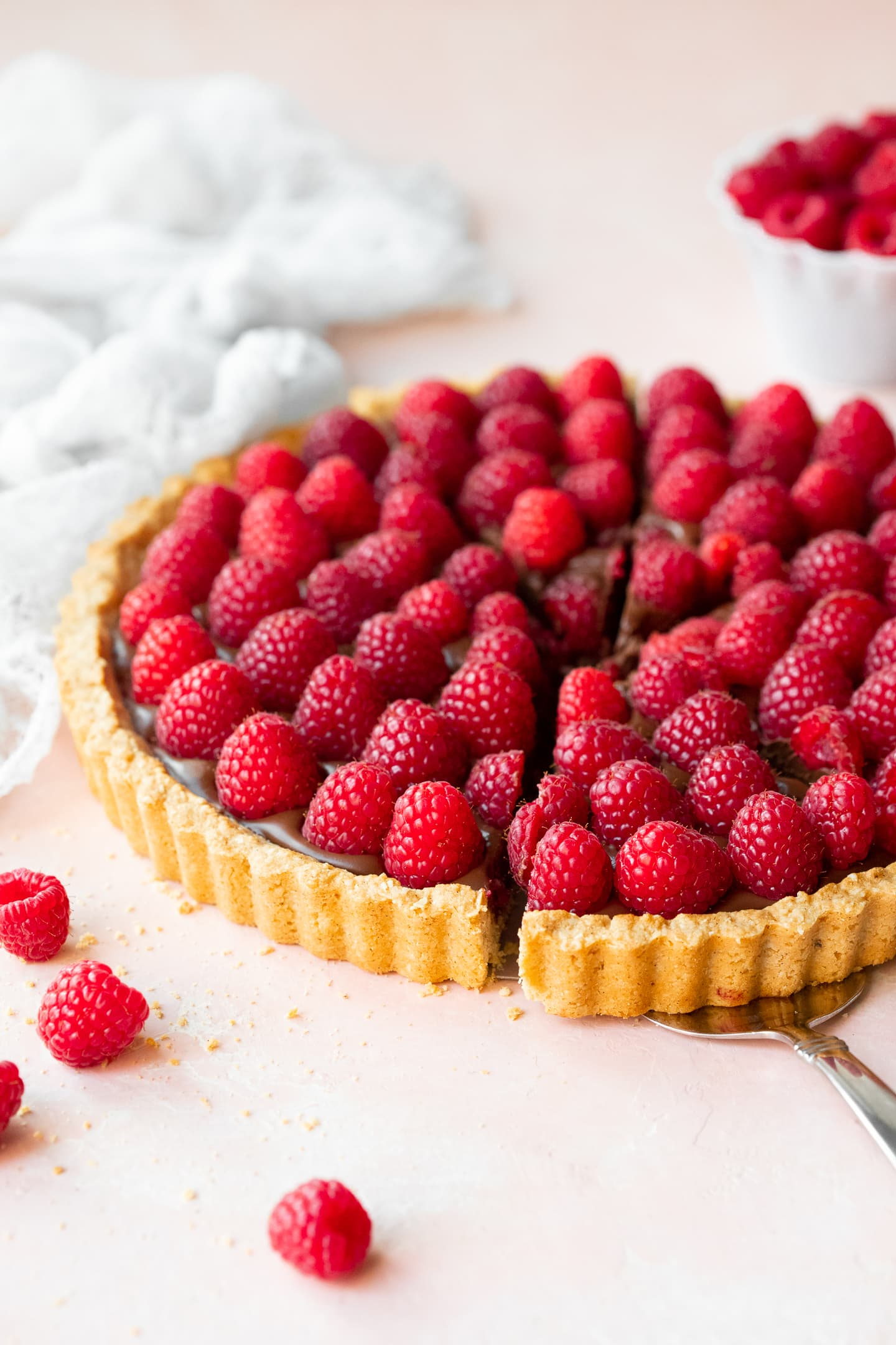 Front-angled view of a raspberry chocolate tart with a slice on a cake server, with scattered raspberries in the foreground and raspberries in a bowl in the background.