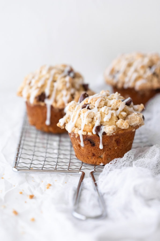 Three gluten-free banana chocolate chip muffins placed on a safety grater over a white backdrop.