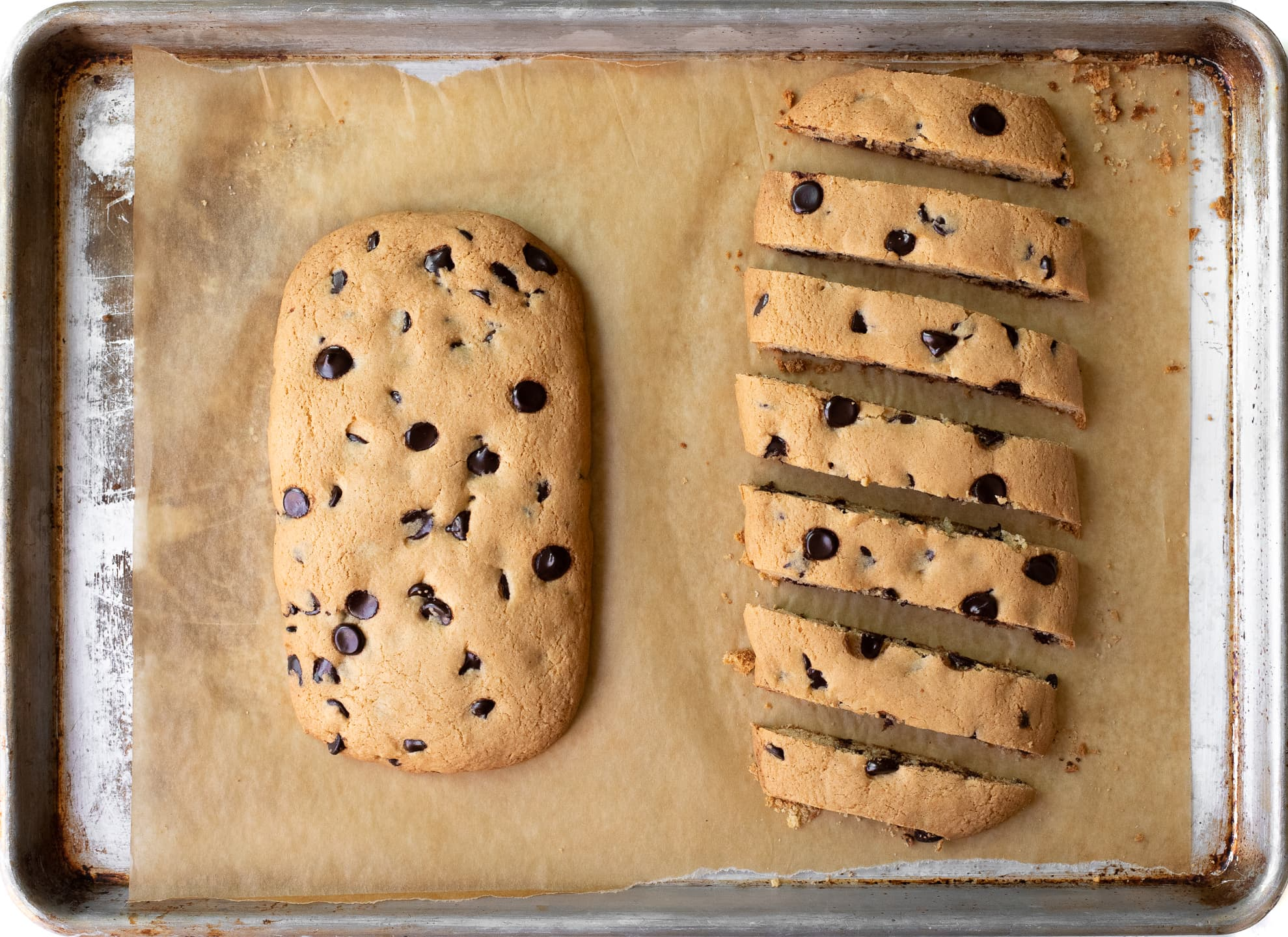 Visual depiction of biscotti dough in the process of being baked and sliced.