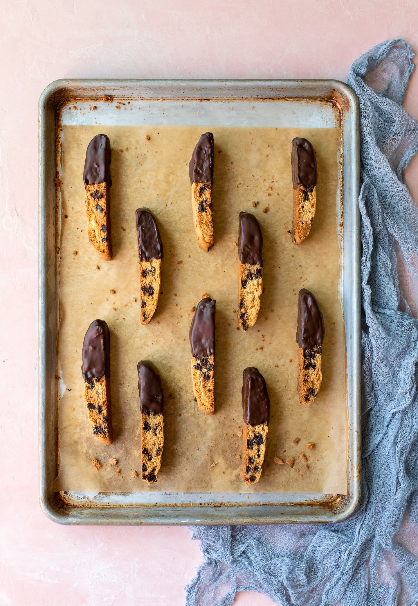 Chocolate chip biscotti dipped in chocolate and arranged on a baking sheet over a light pink backdrop.