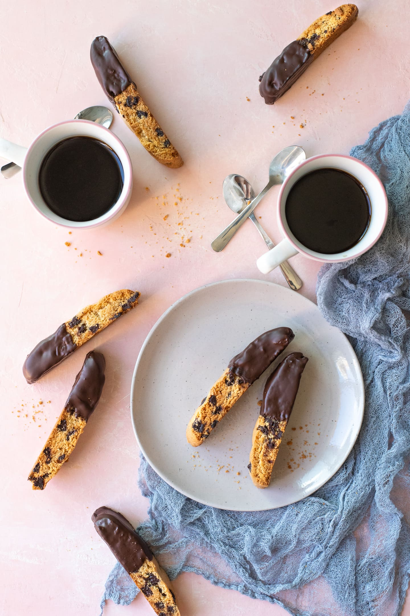 Two chocolate chip biscotti on a grey plate, surrounded by a blue-grey linen, scattered biscotti, and two cups of coffee.