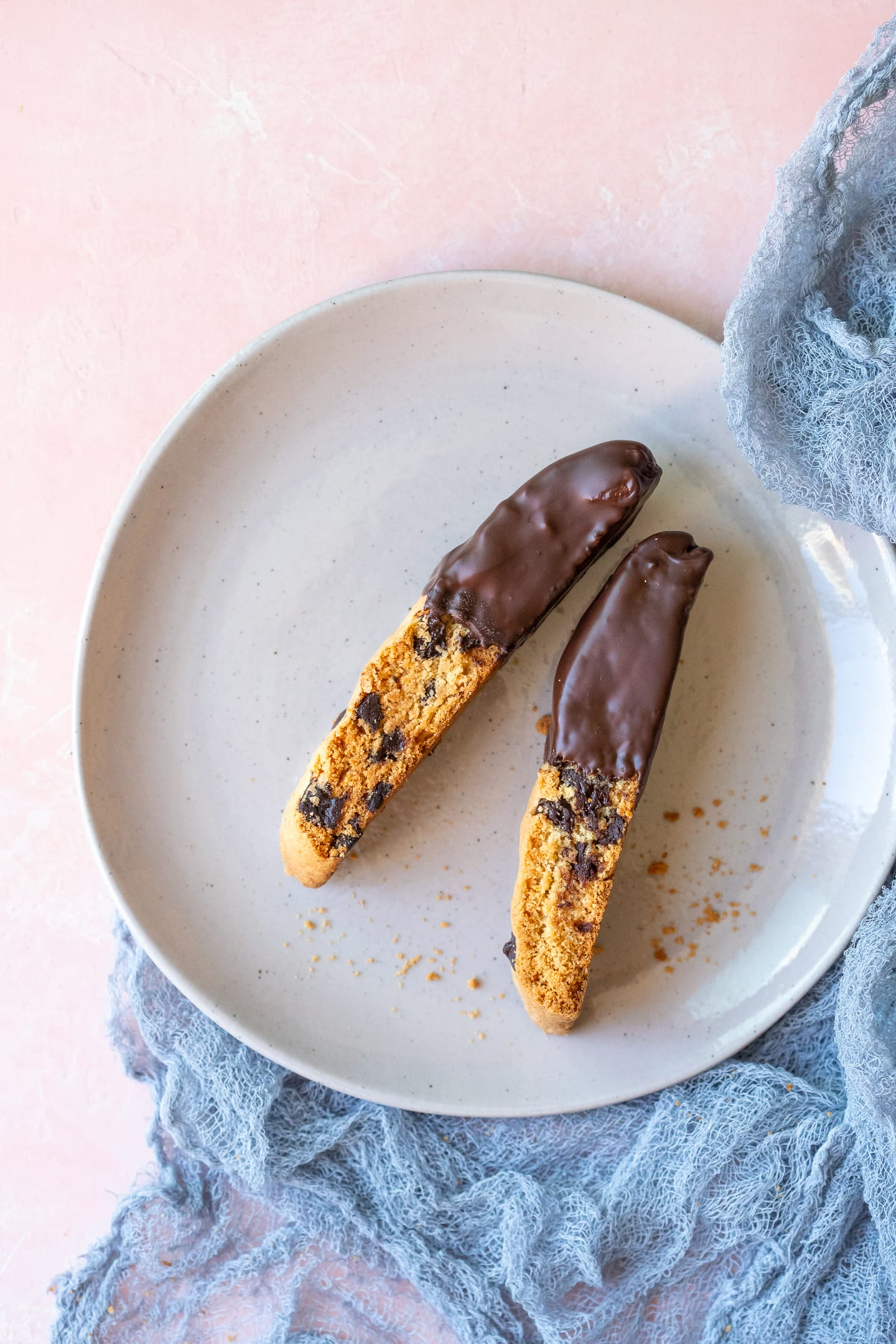 Two chocolate chip biscotti on a grey plate, next to a blue-grey linen, over a light pink backdrop.