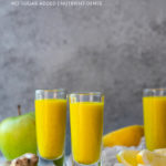 Juice shots surrounded by ingredients against a grey background.