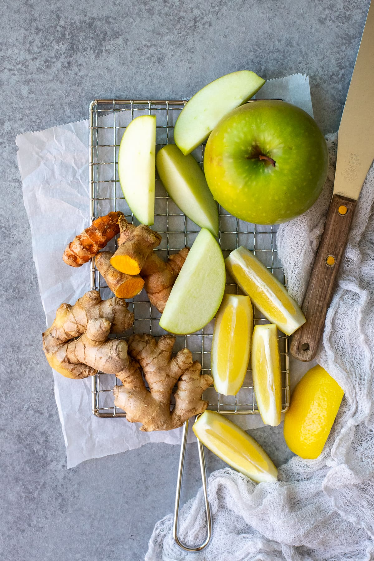 Ingredients being prepped for juicing - apples, lemons, turmeric, and ginger.