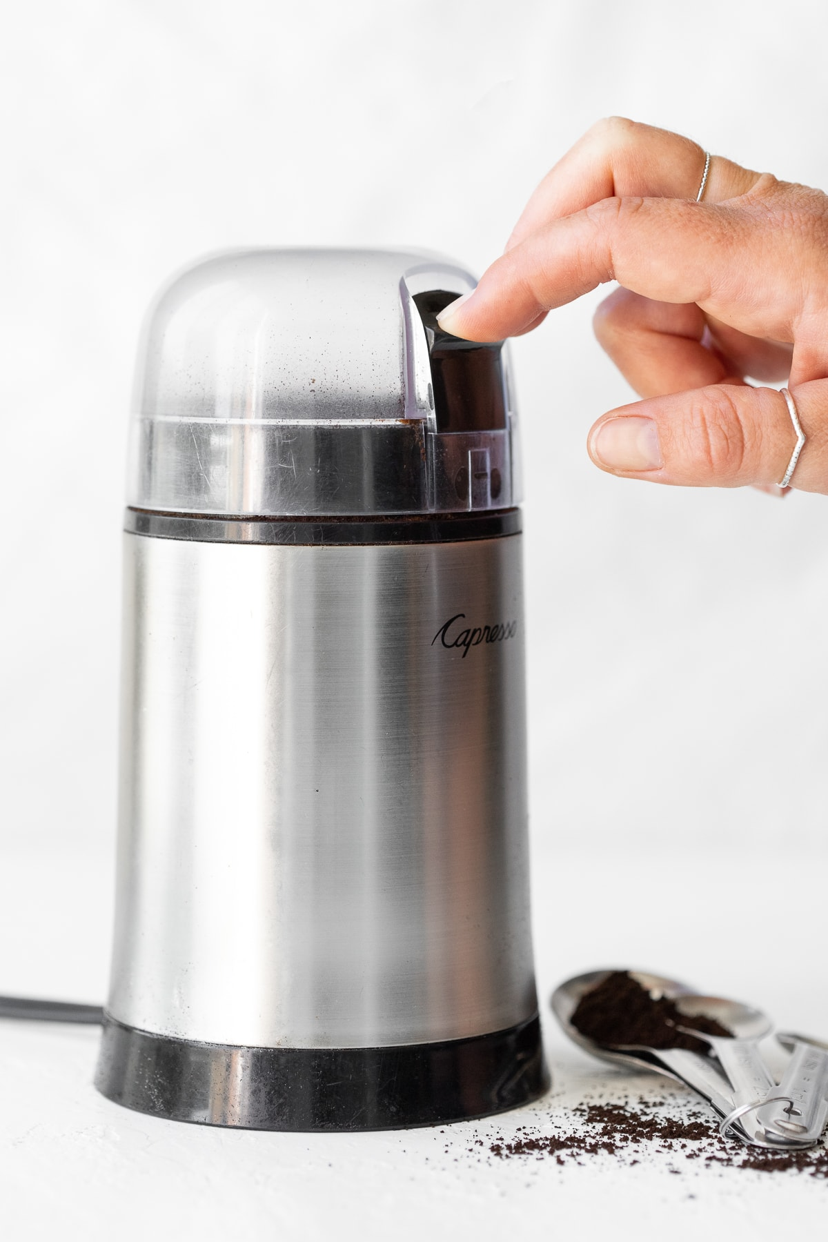 Coffee grinder being used to grind brewed and baked espresso grounds.
