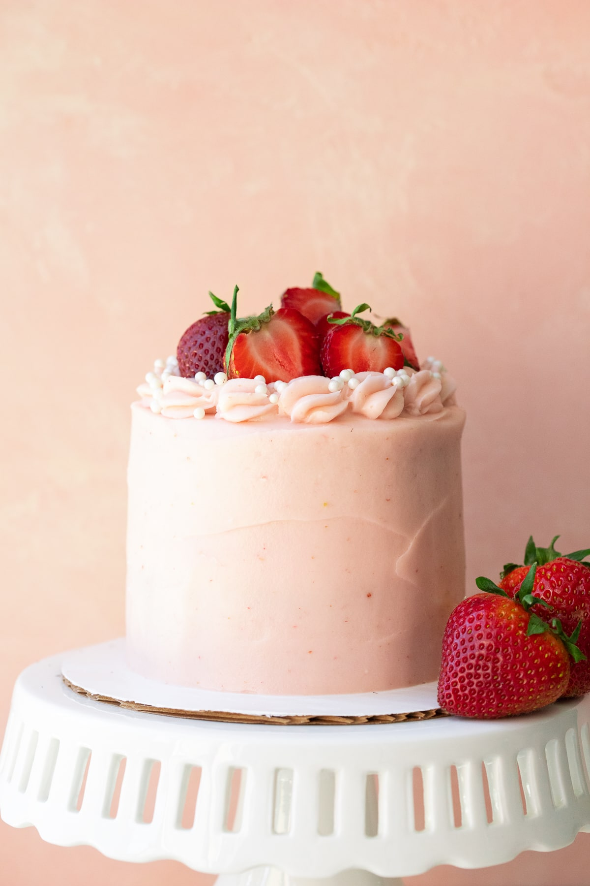 Front-facing view of cake on a white stand with strawberries to the side, against a pink backdrop.